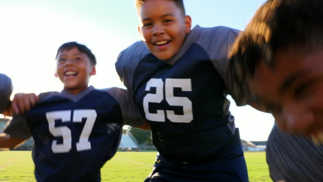 stockvideo's en b-roll-footage met pan smiling and laughing young football teammates with arms around each other huddling before game - alleen kinderen