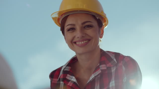 smiling architect working and looking at camera - construction worker stock videos and b-roll footage