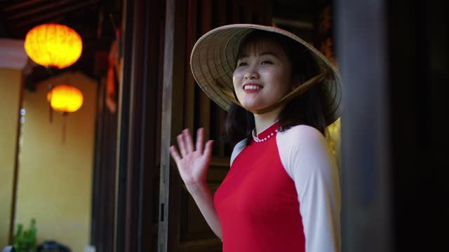 smiling asian girl in traditional dress waving vietnam - 赤のドレス点の映像素材/bロール
