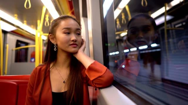 vidéos et rushes de fille asiatique de sourire voyageant par le train - une seule adolescente