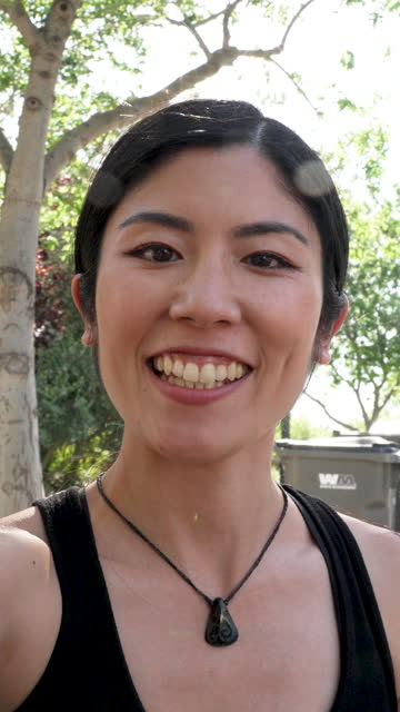 vídeos de stock, filmes e b-roll de mulher asiática asiática sorridente meio adulto vlogging falando com seu telefone inteligente - imagem em movimento