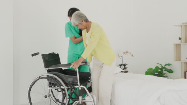 smiling asian nurse assisting senior woman to get up from bed. caring nurse supporting patient while getting up from bed and move towards wheelchair at home. helping elderly disabled woman standing up. - waist stock videos & royalty-free footage