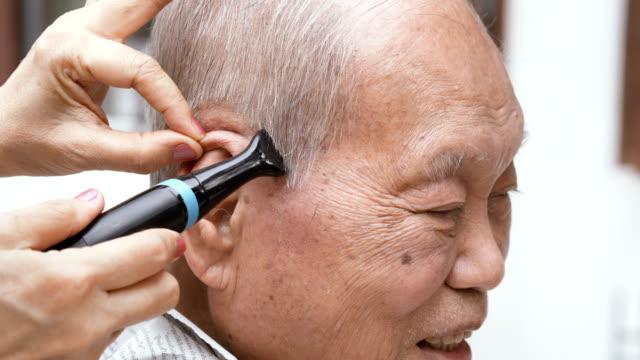 vídeos y material grabado en eventos de stock de hombre senior asiático sonriente que recibe un recorte de cabello - ayudante