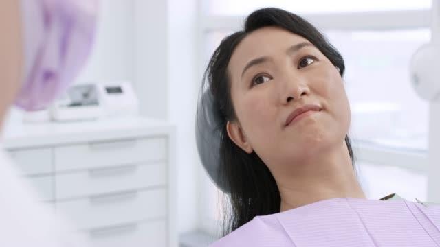 lächelnde asiatische frau liegend in den behandlungsstuhl und im gespräch mit ihrem zahnarzt - weibliche person stock-videos und b-roll-filmmaterial