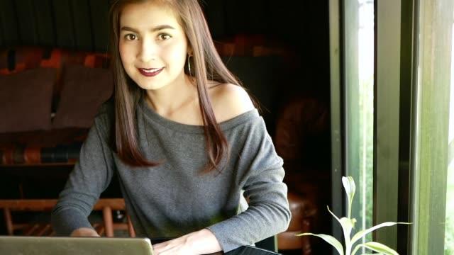 lächelnde asiatische frau mit laptop-computer im coffee shop - weibliche angestellte stock-videos und b-roll-filmmaterial