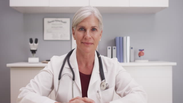 Smiling attractive mature female doctor talking to camera patient POV