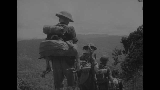 a smiling australian soldier with cloth around his neck / vs low angle view of soldiers walking downhill with the sky beyond and three of the men... - 煙草製品点の映像素材/bロール