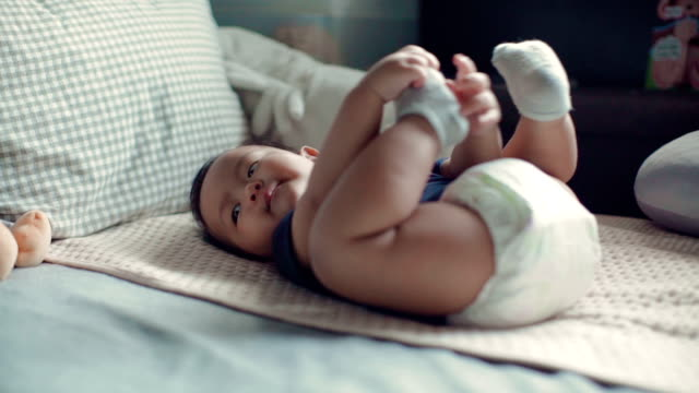 Smiling baby boy lying on the bed in bedroom. Thailand