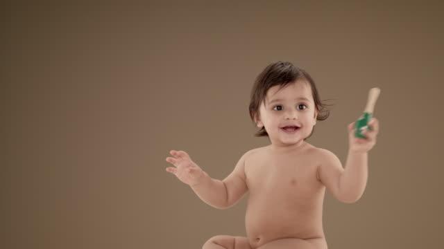 vídeos y material grabado en eventos de stock de smiling baby boy (11-12 months) sitting on floor holding toy - sin camisa