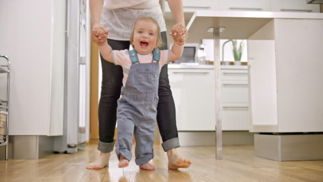 slo mo smiling baby boy walking with his mother's support - primi passi video stock e b–roll