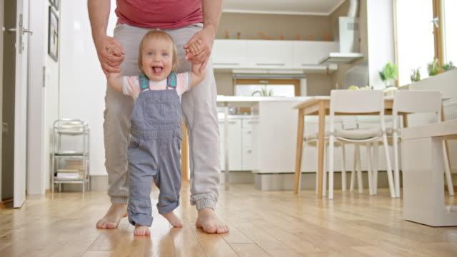 vídeos de stock, filmes e b-roll de slo mo sorridente menino andando com a ajuda de seu pai - criança pequena