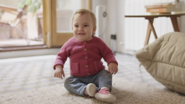 smiling baby girl crawling on carpet at home - baby clothing stock videos & royalty-free footage