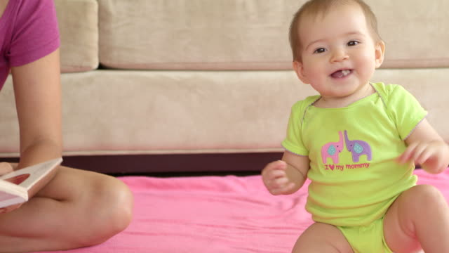 Smiling Baby Girl Sitting on Pink Blanket