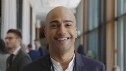 Smiling bald businessman at seminar in hotel