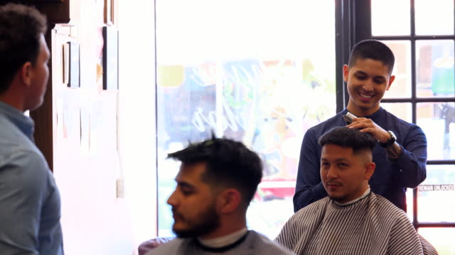 MS Smiling barber in discussion with coworker while cutting clients hair