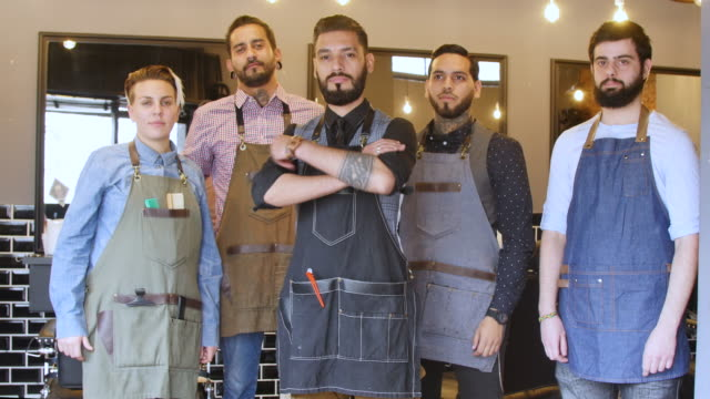 smiling barber standing arms crossed with his team - hairdresser stock videos & royalty-free footage