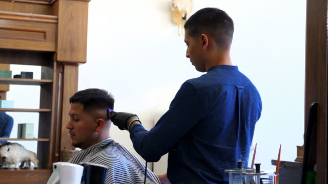 ms smiling barber using trimmers to cut mans hair in barber shop - hair clipper stock videos & royalty-free footage