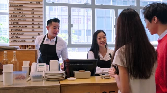 smiling barista giving coffee to customers - dinner lady stock videos & royalty-free footage