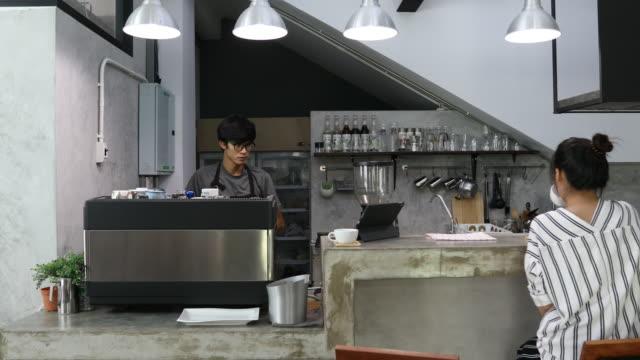 Smiling barista serving a client