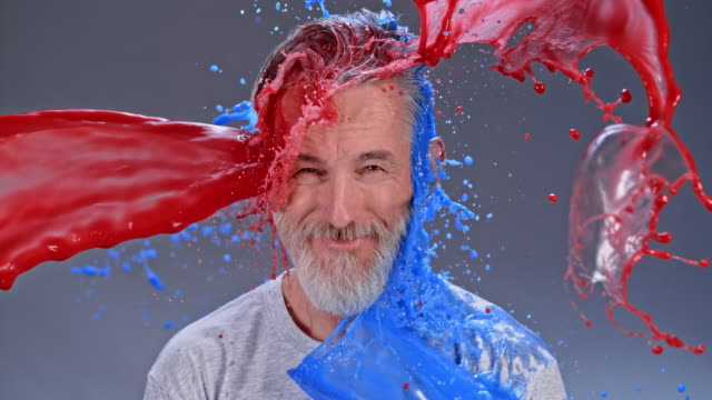 slo mo ld smiling bearded man being hit by a red and blue color splash - brown eyes stock videos & royalty-free footage