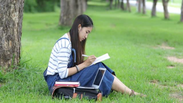 vídeos de stock, filmes e b-roll de livro de leitura da bela garota asiática a sorrir e trabalhando em uma árvore no parque no verão para relaxar tempo - sentando