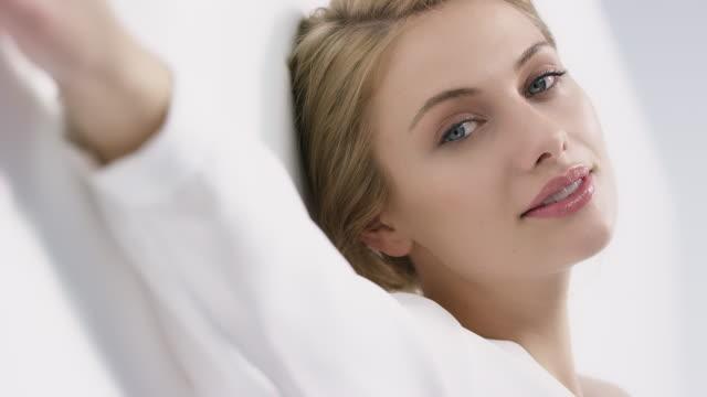 bella donna sorridente appoggiata al muro - persona attraente video stock e b–roll