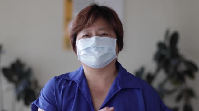 lächeln hinter der maske - malaysian culture stock-videos und b-roll-filmmaterial