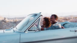 Smiling black couple driving on a desert highway, close up