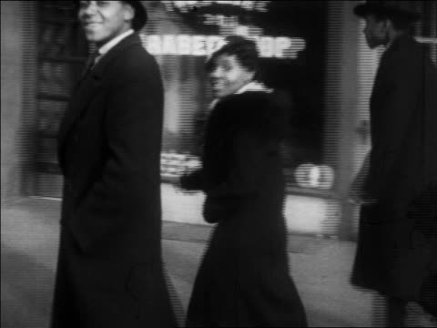 vídeos y material grabado en eventos de stock de b/w 1930 pan smiling black couple walking by camera on harlem sidewalk / nyc / newsreel - 1930