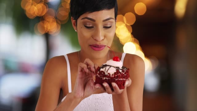 smiling black female eating fancy cupcake in outdoor setting with bokeh lights - vergnügen stock-videos und b-roll-filmmaterial