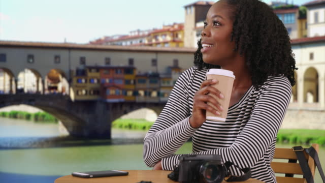 smiling black female sits outdoors enjoying view of ponte vecchio bridge - ponte点の映像素材/bロール