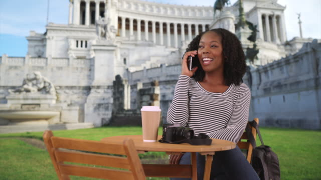 smiling black woman sits at table outside piazza venezia chatting on phone - african american culture stock videos & royalty-free footage
