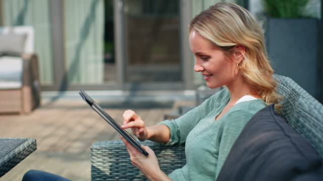 smiling blond woman using digital tablet at patio - patio stock videos & royalty-free footage
