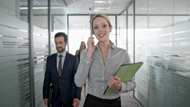 Smiling blonde Caucasian businesswoman talking on the phone while walking in office hallway past her coworkers