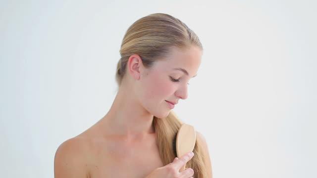 Smiling blonde woman brushing her hair
