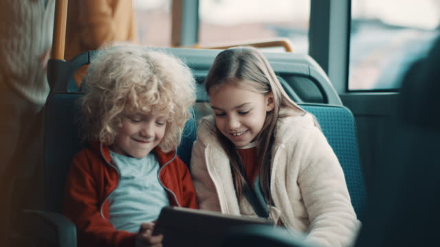 smiling boy and a girl using tablet together in the bus - vehicle seat stock videos & royalty-free footage