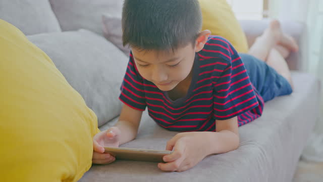 smiling boy enjoy watching and playing on mobile phone in the living room at home. - digital native stock videos & royalty-free footage