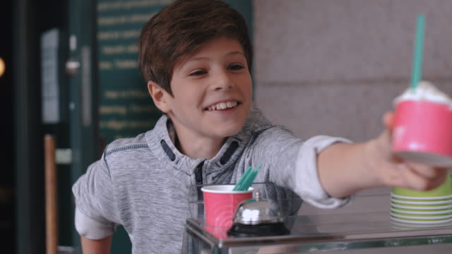 smiling boy giving ice cream cup to customer at stand in city - stockholm stock-videos und b-roll-filmmaterial