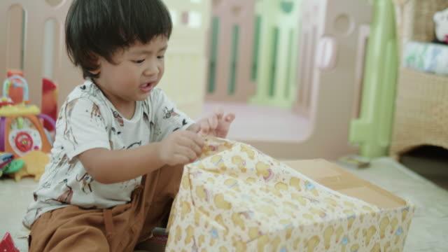 微笑む少年の誕生日ギフト ボックスを開きます。 - 小荷物点の映像素材/bロール