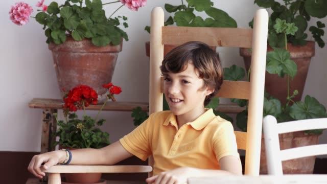 stockvideo's en b-roll-footage met lachende jongen rustend op schommelstoel tegen potten - schommelen schommelstoel