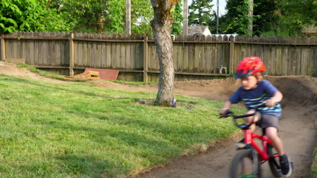 ms smiling boy riding bmx bike on backyard dirt track on a summer afternoon - bmx cycling stock videos and b-roll footage
