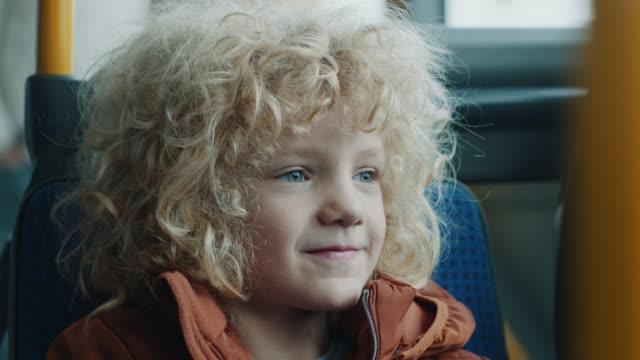 leende pojke rida på bussen - spårvagn bildbanksvideor och videomaterial från bakom kulisserna