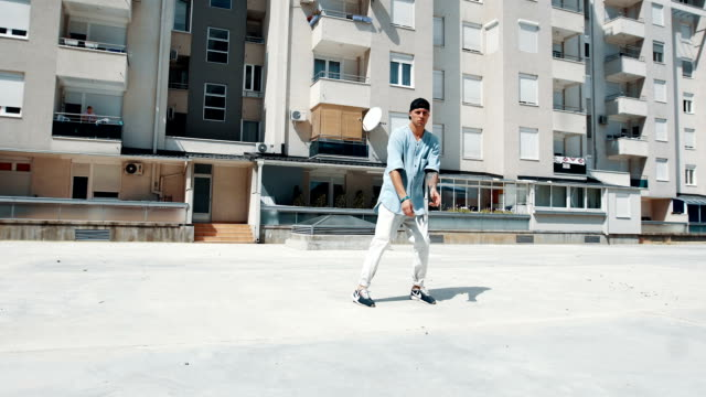 smiling break dancer dancing in front of the building - tipo di danza video stock e b–roll
