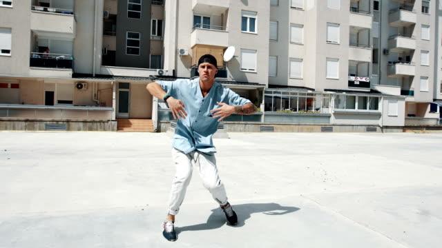 vídeos y material grabado en eventos de stock de sonriente bailarina rompe bailando frente al edificio - ancho