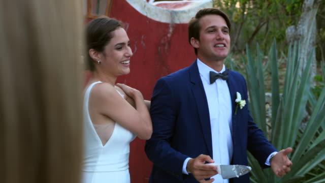 ms smiling bride and groom cutting cake during outdoor wedding reception - 礼拝堂点の映像素材/bロール