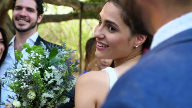 MS Smiling bride and groom in discussion with wedding guests after outdoor ceremony