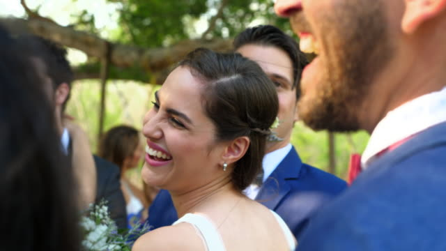 vídeos de stock, filmes e b-roll de cu smiling bride in discussion with family and friends after wedding ceremony at destination resort - bride