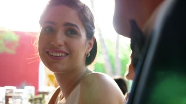 vídeos de stock, filmes e b-roll de ms smiling bride in discussion with groom during dinner at destination wedding - bride