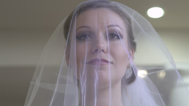 vídeos de stock, filmes e b-roll de smiling bride wearing wedding dress, lifting veil. - véu