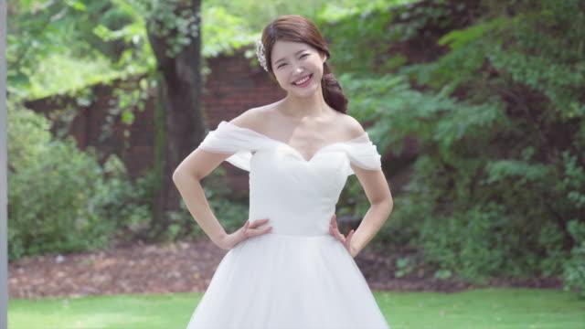vídeos y material grabado en eventos de stock de a smiling bride with her hands on her waist an outdoor wedding studio - sólo mujeres jóvenes